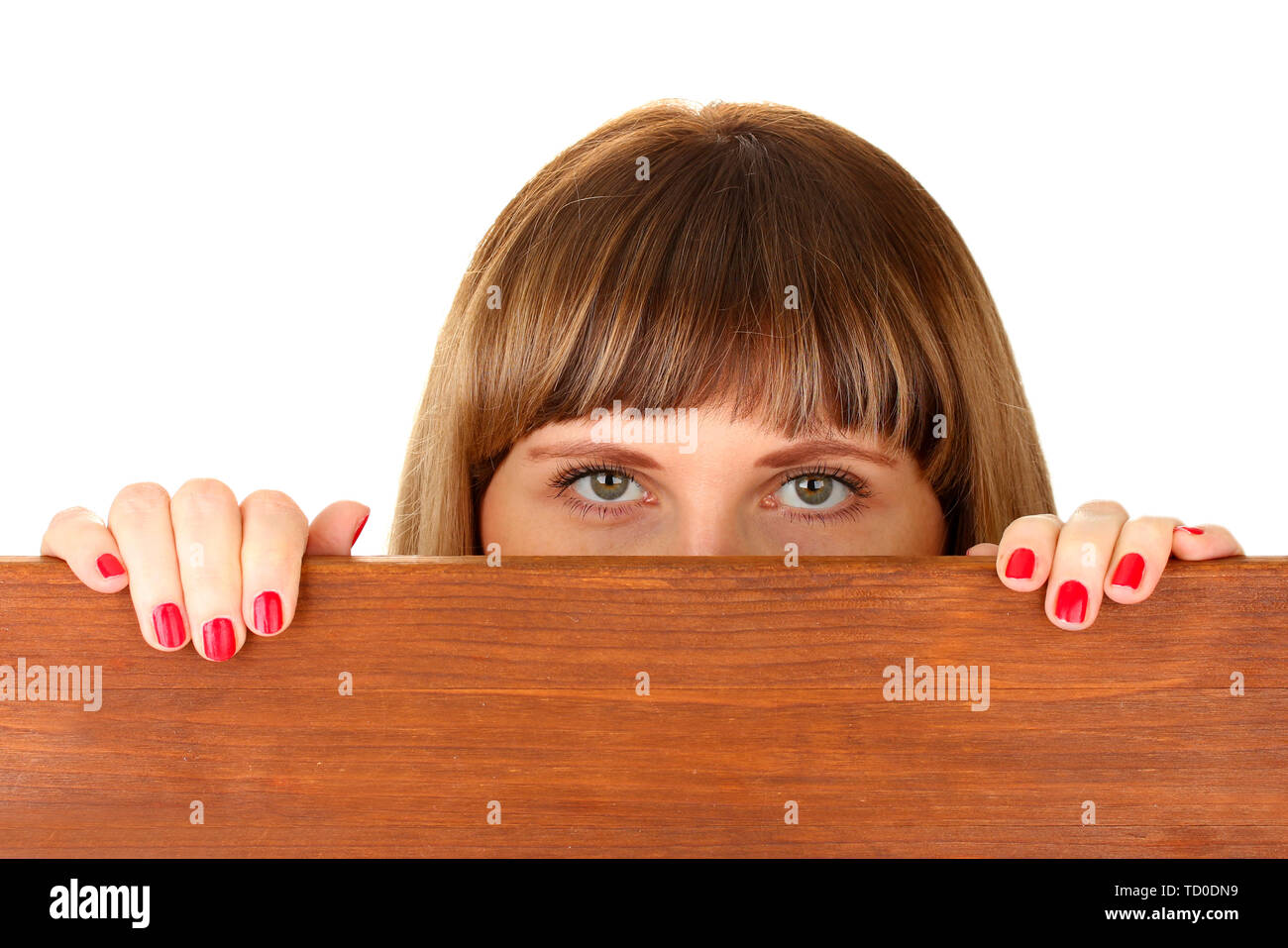 Woman peeking from wooden desk, isolated on white - Stock Image