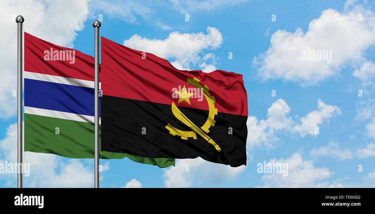 Gambia and Angola flag waving in the wind against white cloudy blue sky together. Diplomacy concept, international relations. Stock Photo