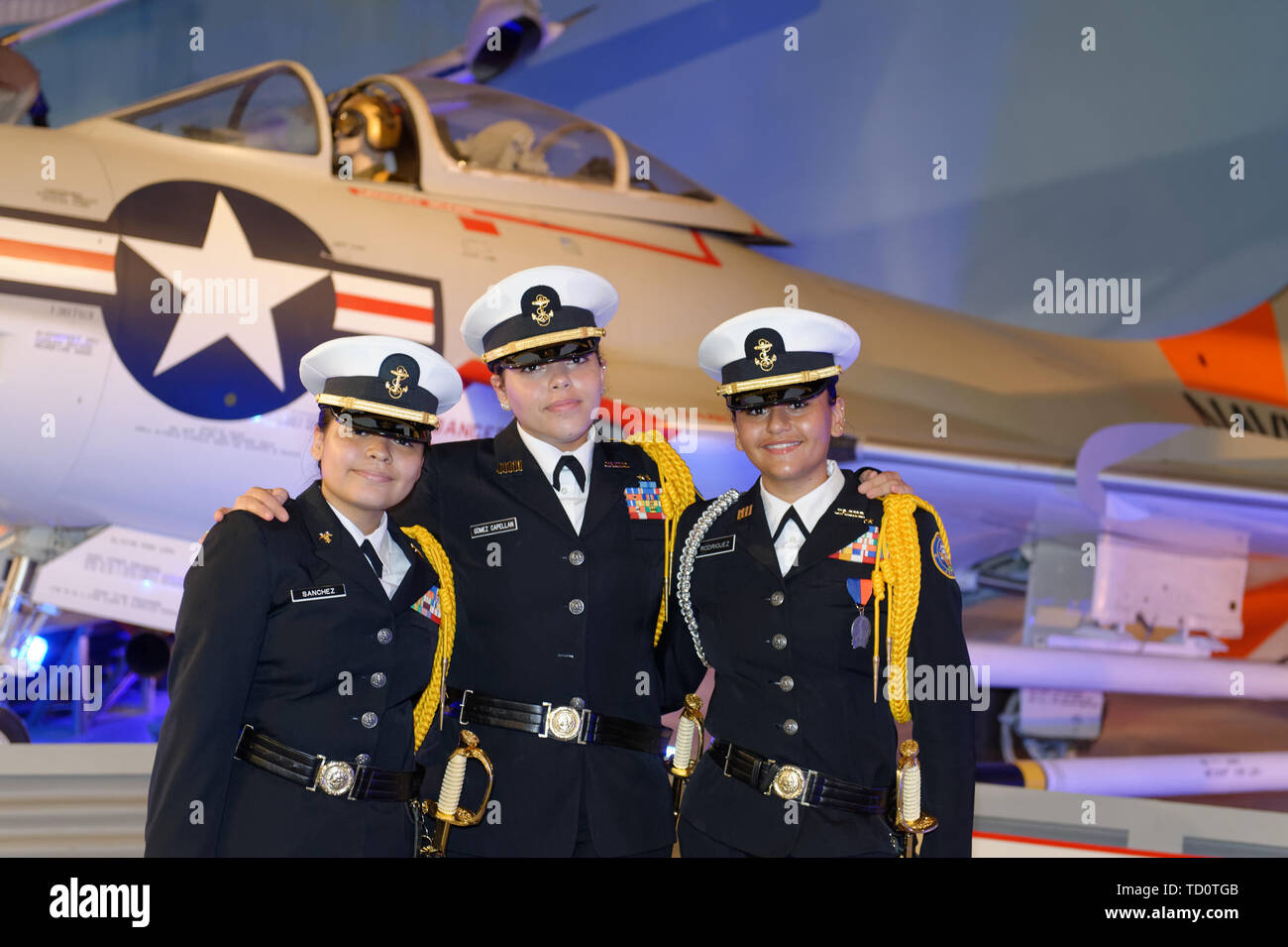 Garden City, New York, USA. 6th June, 2019. Three Freeport High School Navy Junior ROTC cadets wearing uniforms and about to participate at Apollo at 50 Anniversary Dinner at Cradle of Aviation Museum, pose for photo in front of historic aircraft at museum exhibit. Credit: Ann Parry/ZUMA Wire/Alamy Live News - Stock Image