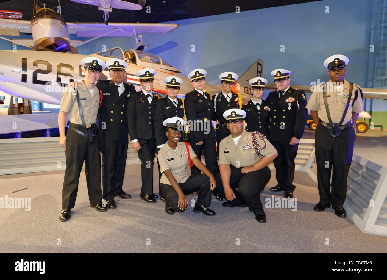 Garden City, New York, USA. 6th June, 2019. Freeport High School Navy Junior ROTC cadets wearing uniforms and about to participate at Apollo at 50 Anniversary Dinner at Cradle of Aviation Museum, pose for photo in front of historic aircraft at museum exhibit. Credit: Ann Parry/ZUMA Wire/Alamy Live News - Stock Image