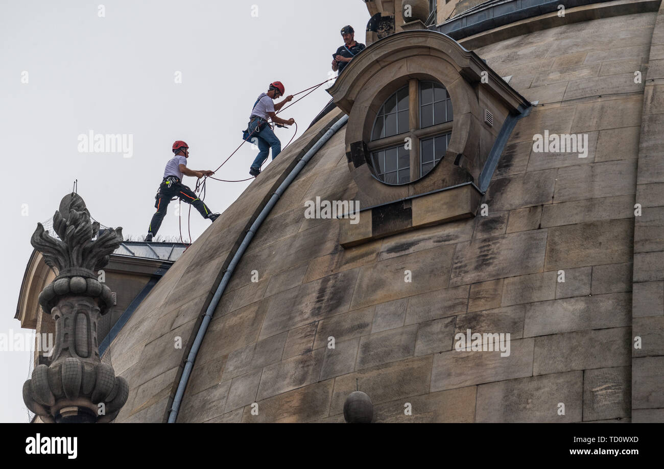 Dresden, Germany. 11th June, 2019. Height workers climb on the dome of the Frauenkirche to renew lights for the evening illumination of the stone dome. Maintenance and replacement work has to be carried out on a total of 40 luminaires on the lantern shaft, the small dome buildings and the rear sides of the staircase tower. The work is necessary because the light from the previous luminaires no longer reflects sufficiently from the darkening stone. Credit: Robert Michael/dpa-Zentralbild/dpa/Alamy Live News - Stock Image