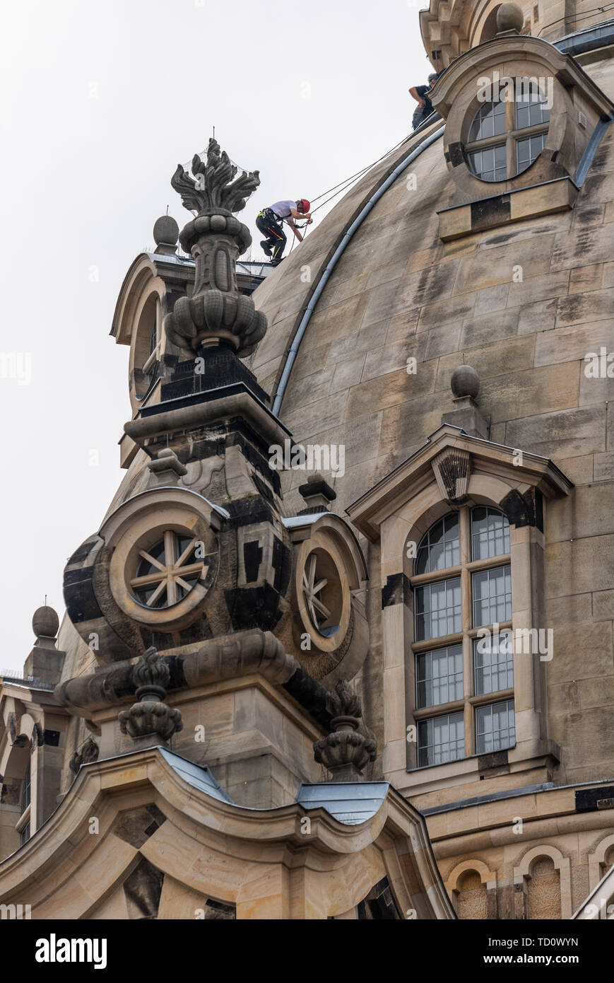 Dresden, Germany. 11th June, 2019. A rope access technician climbs on the dome of the Frauenkirche to renew lights for the evening illumination of the stone dome. Maintenance and replacement work has to be carried out on a total of 40 luminaires on the lantern shaft, the small dome buildings and the rear sides of the staircase tower. The work is necessary because the light from the previous luminaires no longer reflects sufficiently from the darkening stone. Credit: Robert Michael/dpa-Zentralbild/dpa/Alamy Live News - Stock Image