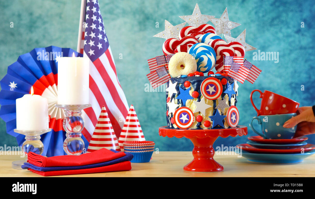 USA theme on-trend candyland fantasy drip cake with decorations in colorful party table setting. - Stock Image
