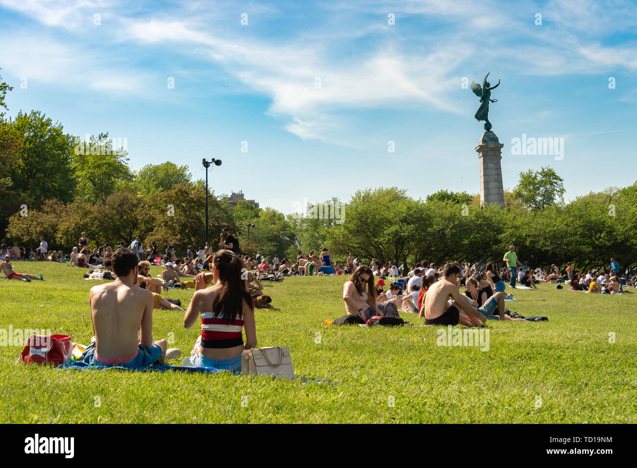 Montreal, 10 June 2019: Locals and tourists enjoy the nice weather and take a sunbath in the Mont-Royal park. - Stock Image