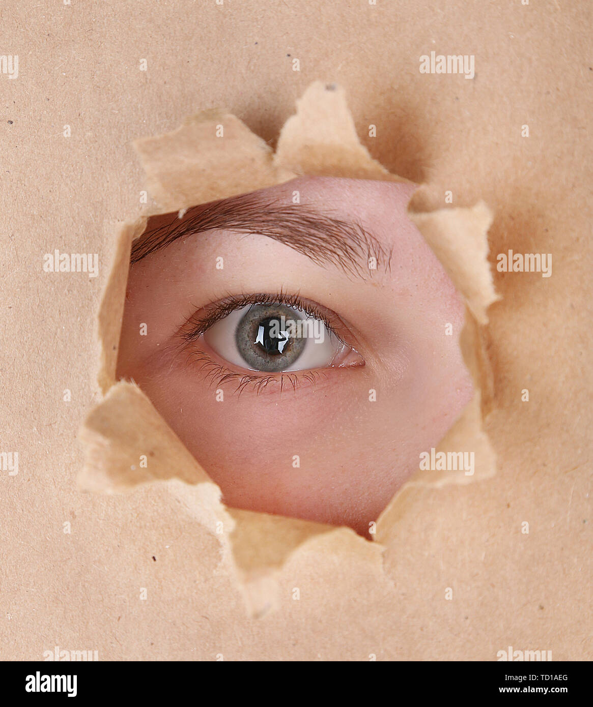 Female eye looking through hole in sheet of paper - Stock Image