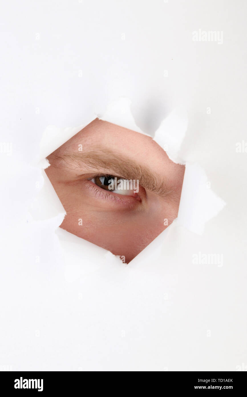 Man eye looking through hole in sheet of paper - Stock Image