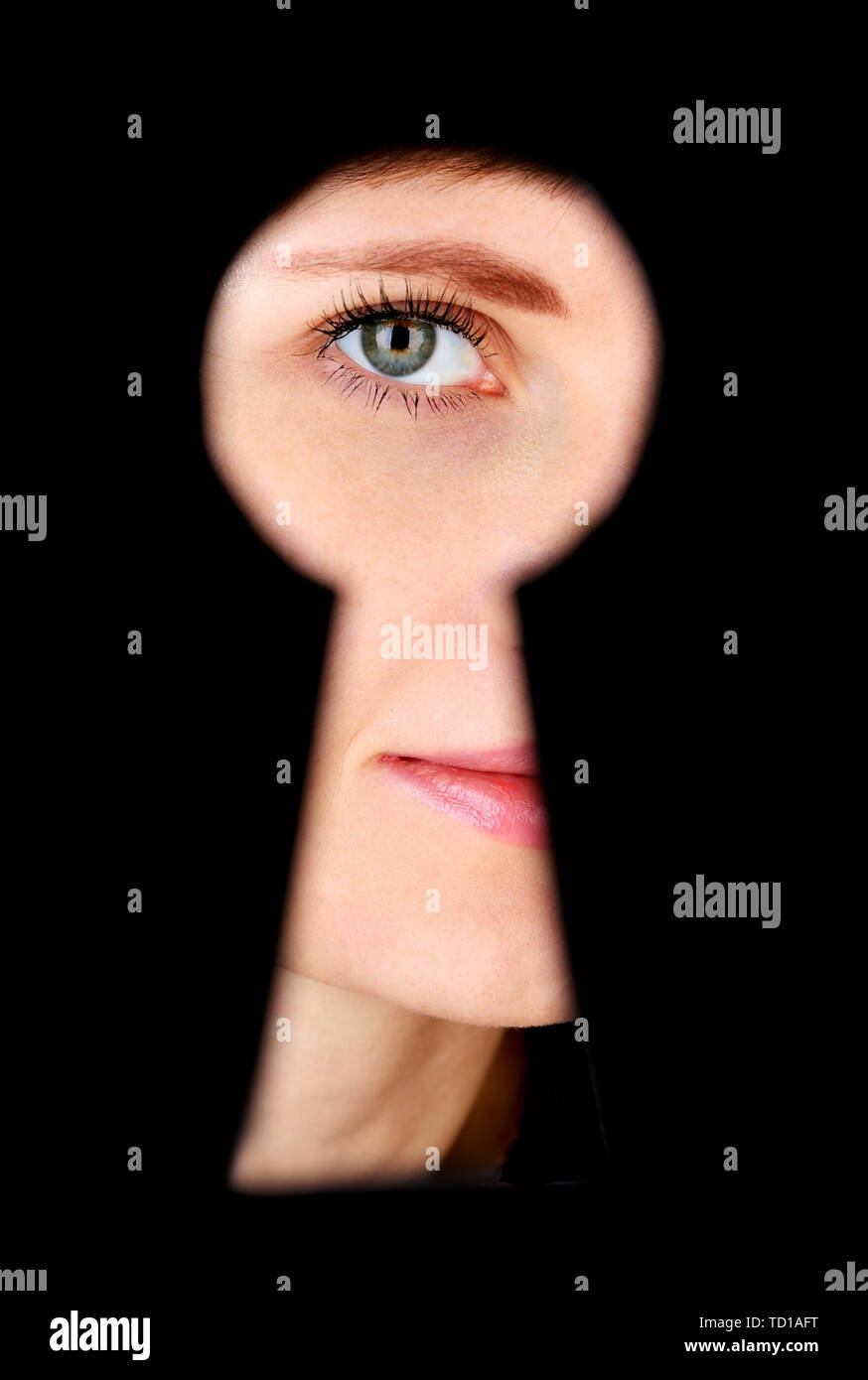 Woman eye looking through hole in keyhole, on black background - Stock Image