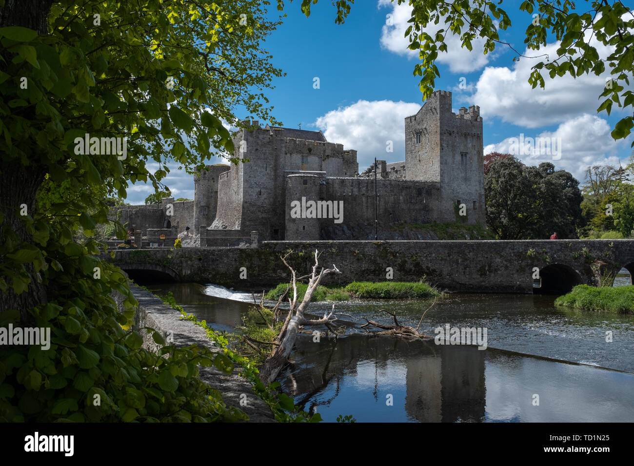 A view of the Castle of Cahir across the weir down the River Suir, bright blue sky and fluffy white clouds, nobody in the image - Stock Image