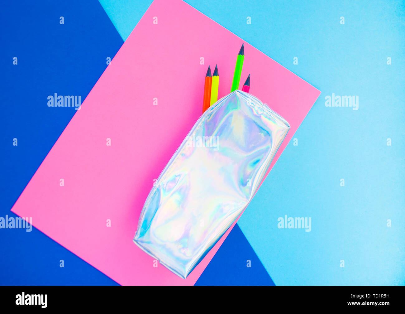 Colorful paper, neon pencils and holographic pencil case on blue and pink background. Flat lay style. Back to school concept. - Stock Image