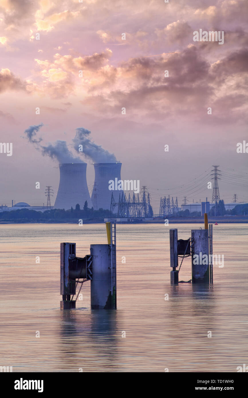Riverbank with nuclear power plant Doel during a sunset with dramatic cluds, Port of Antwerp, Belgium - Stock Image