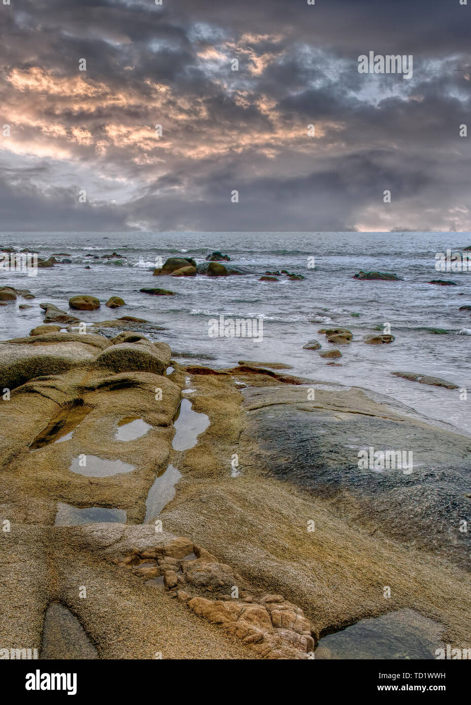 Tranquil seashore with rocks just before a storm, Hainan Island, China - Stock Image