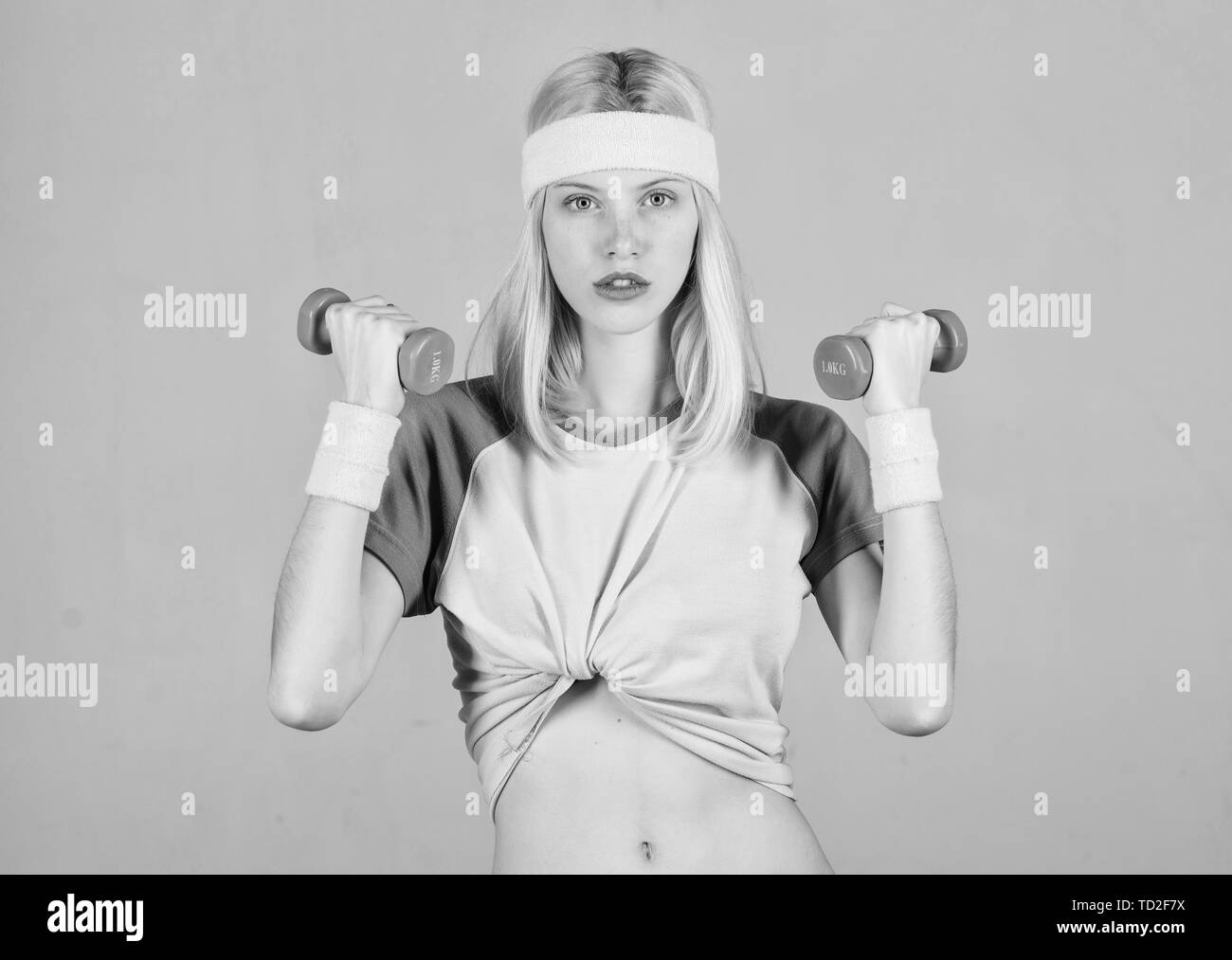 Woman workout in gym with sport equipment. Woman fitness coach exercising with dumbbell. Easy biceps exercise. Workout result. Find personal trainer. Workout with dumbbell. Workout sport and dieting. - Stock Image