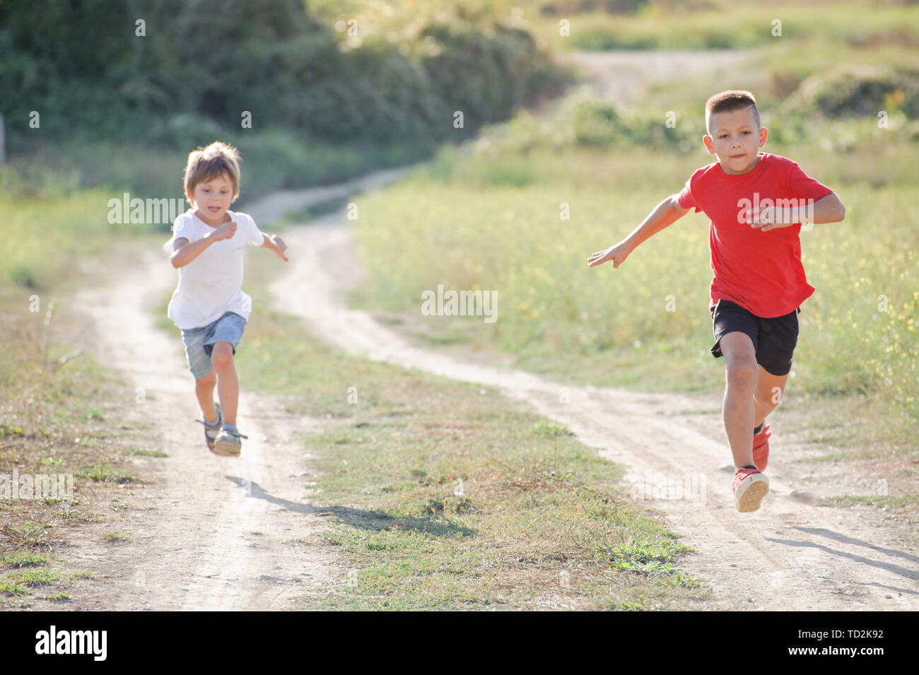 running pursuit two caucasian healthy sport kids boys running together  outdoor summer vacation activity Stock Photo - Alamy