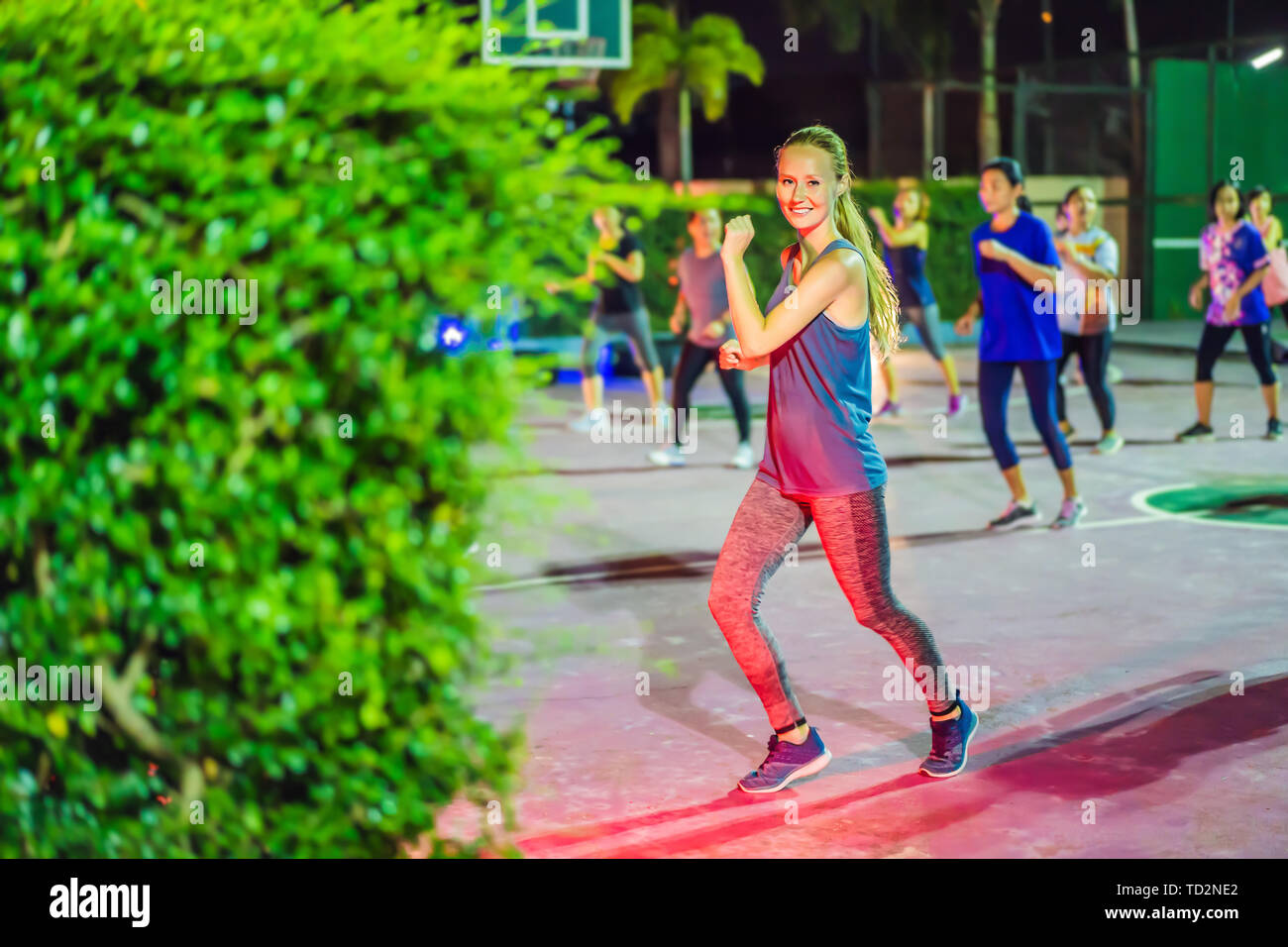 Young woman on a group workout on the basketball court in the evening - Stock Image