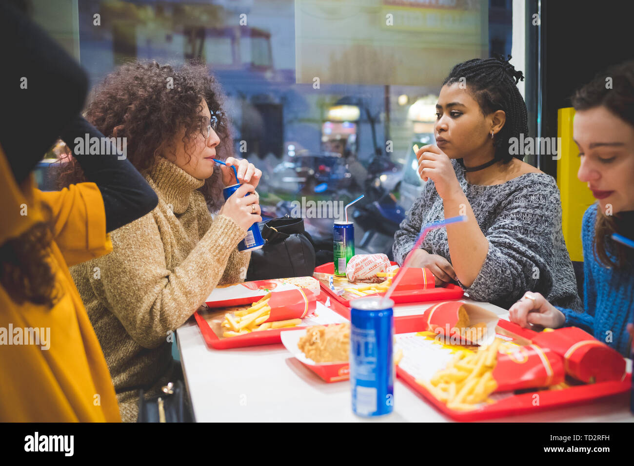 group of young multiracial women eating in fast food and having conversation – break time, conviviality, communication - Stock Image
