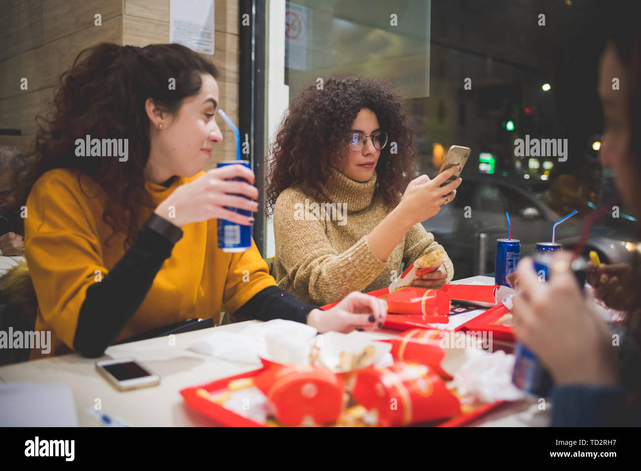 group of young women eating in fast food and interacting with smartphone – break time, conviviality, technology - Stock Image