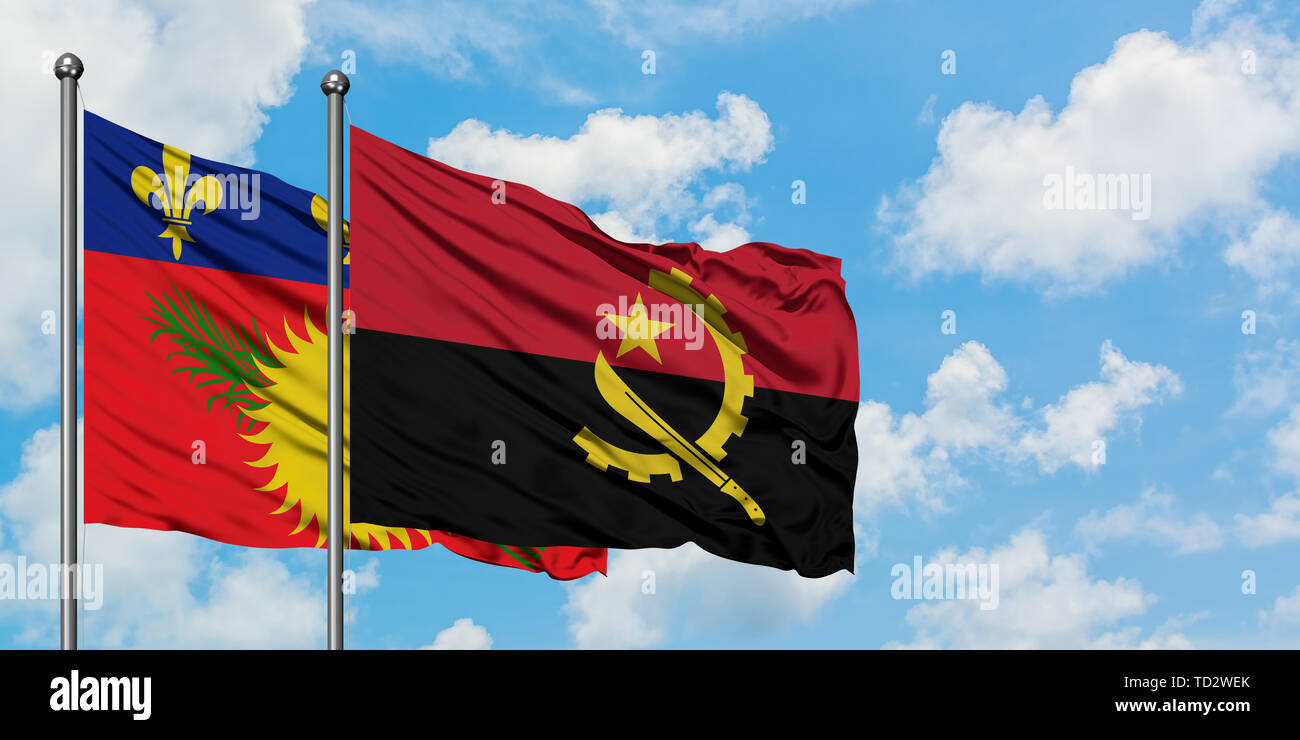 Guadeloupe and Angola flag waving in the wind against white cloudy blue sky together. Diplomacy concept, international relations. - Stock Image