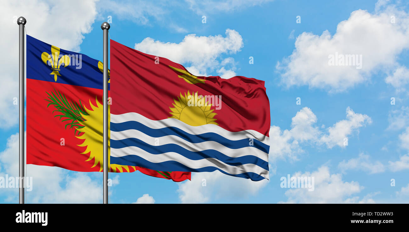 Guadeloupe and Kiribati flag waving in the wind against white cloudy blue sky together. Diplomacy concept, international relations. - Stock Image