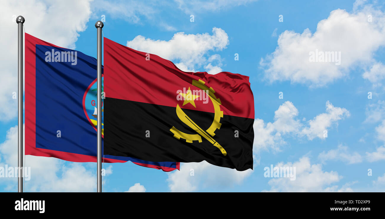Guam and Angola flag waving in the wind against white cloudy blue sky together. Diplomacy concept, international relations. - Stock Image