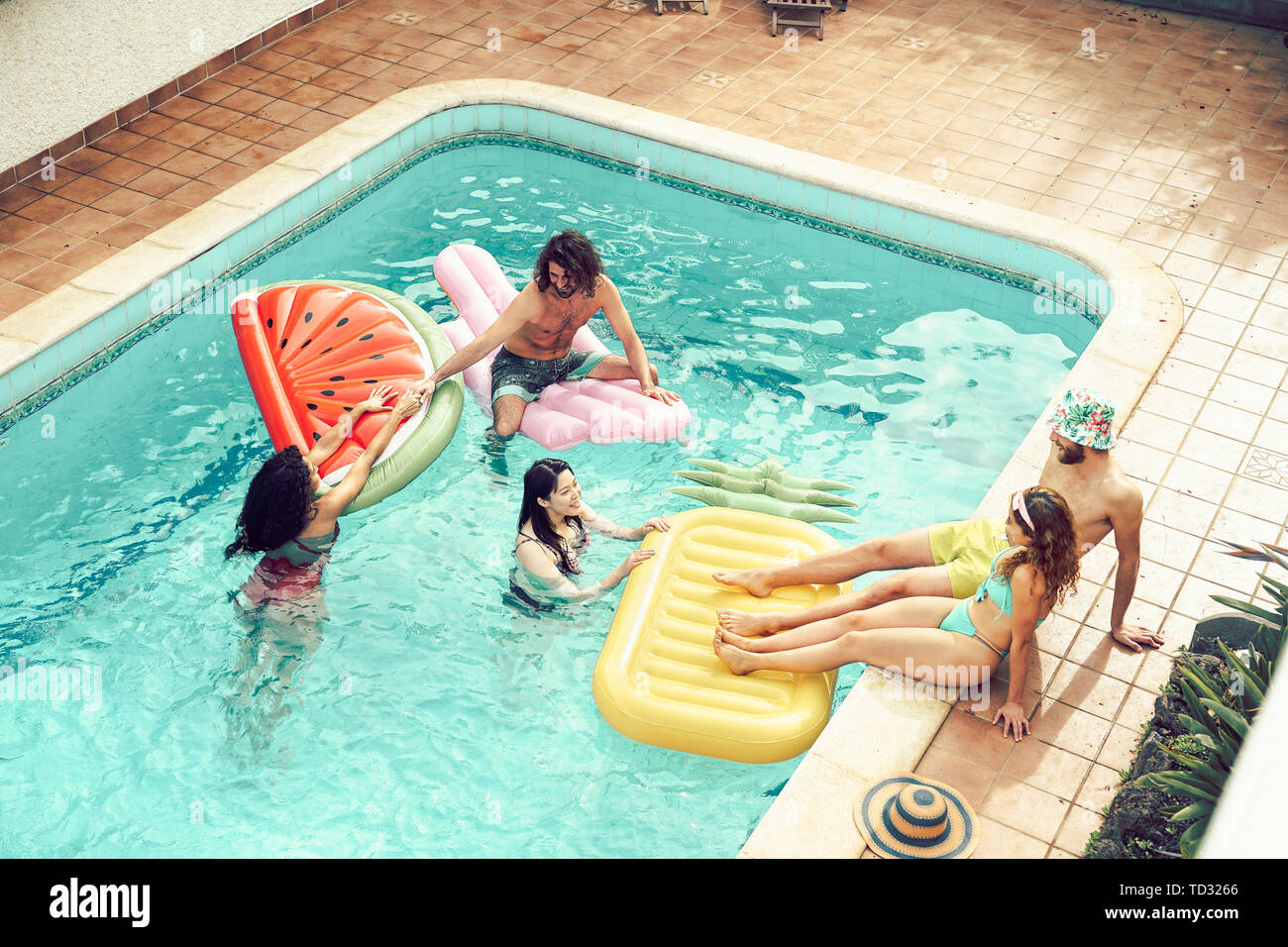 Happy friends having fun in swimming pool during summer vacation - Young people relaxing and floating on air lilos in the pool resort Stock Photo
