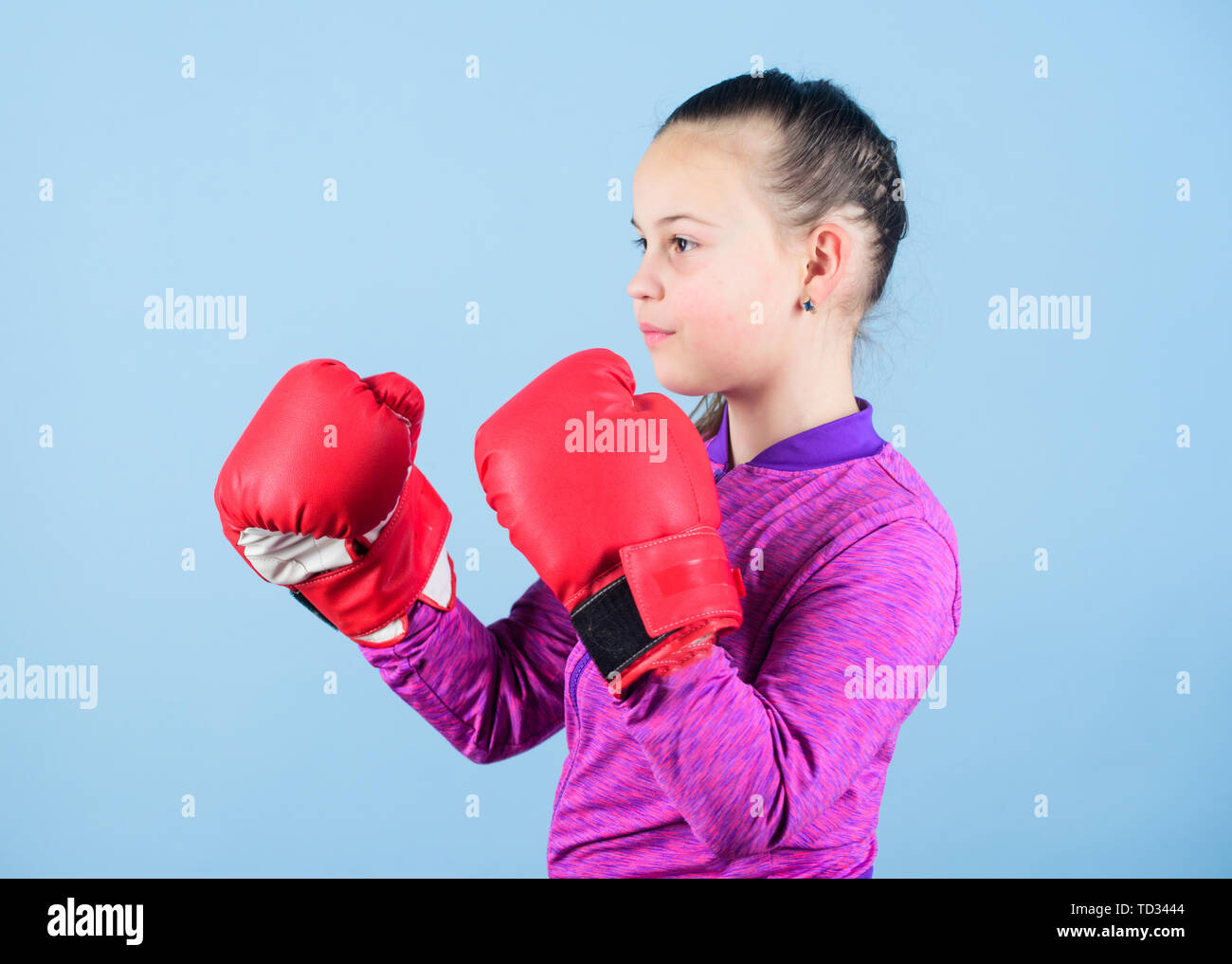 Girl cute boxer on blue background. Contrary to stereotype. Boxer child in boxing gloves. Confident teen. Enjoyment from sport. Female boxer. Sport upbringing. Boxing provide strict discipline. - Stock Image