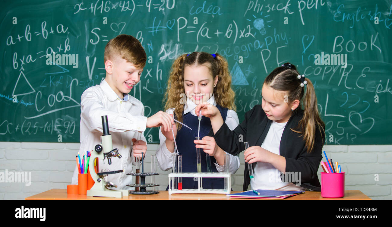Group school pupils study chemistry in school. Boy and girls enjoy chemical experiment. Organic chemistry is study of compounds containing carbon. Basic chemical reactions. Fascinating chemistry. Stock Photo
