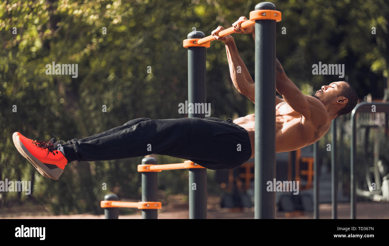 Strong Man Doing Statics Exercise On Horizontal Bar - Stock Image