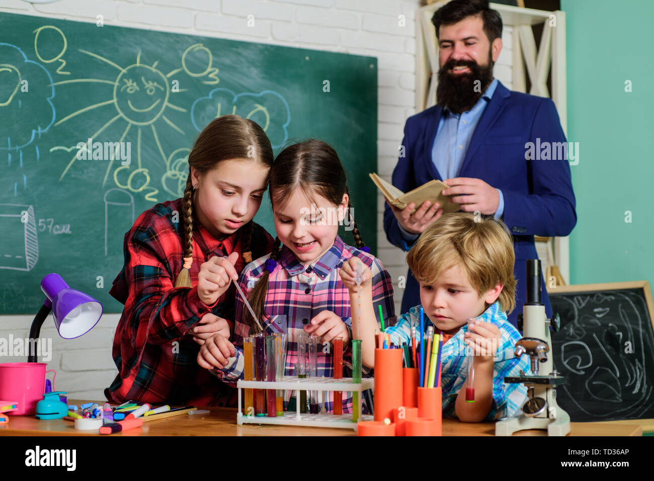 children making science experiments. Education. Science and education. chemistry lab. happy children teacher. back to school. doing experiments with liquids in chemistry lab. Studying hard. - Stock Image
