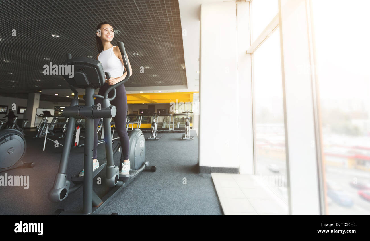 Workout in gym. Woman exercising on cross trainer - Stock Image