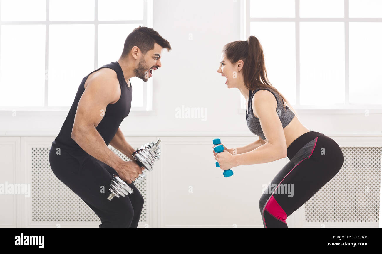 Active couple hardly working out and looking at each other - Stock Image