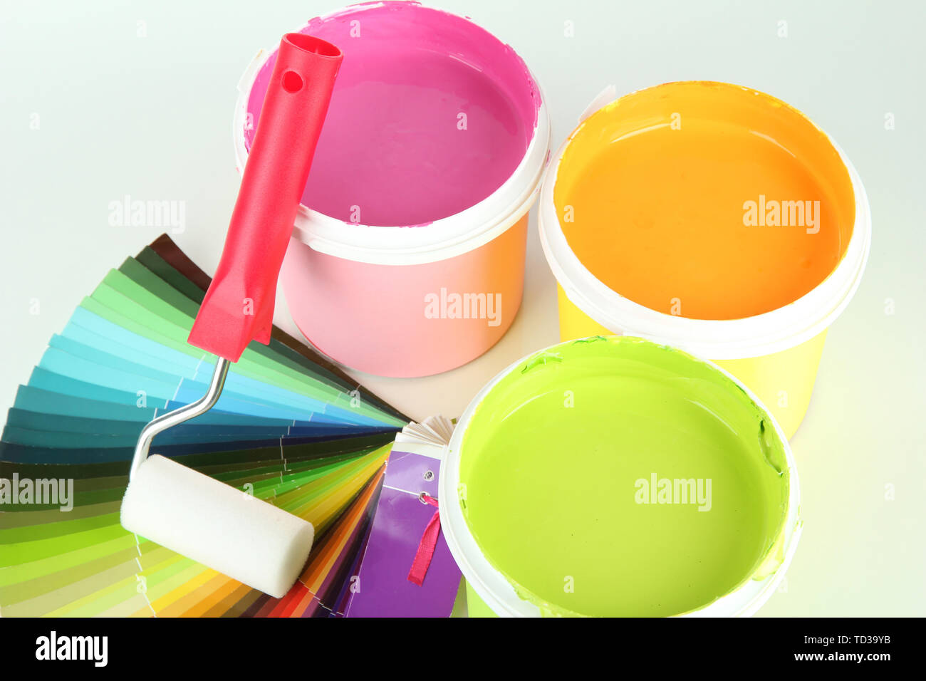 Set for painting: paint pots, paint-roller and palette of colors isolated on white - Stock Image