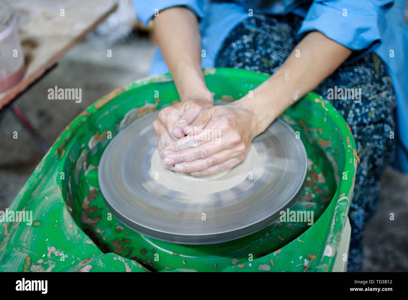 A novice student in the first lesson in pottery tries to make a product from clay on a potter's wheel. reportage. clay centering. Incorrect hand setti Stock Photo