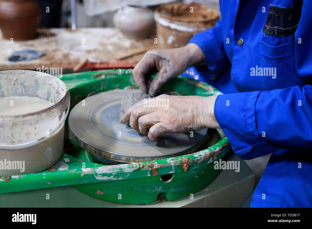 A novice student in the first lesson in pottery tries to make a product from clay on a potter's wheel. reportage. Stock Photo
