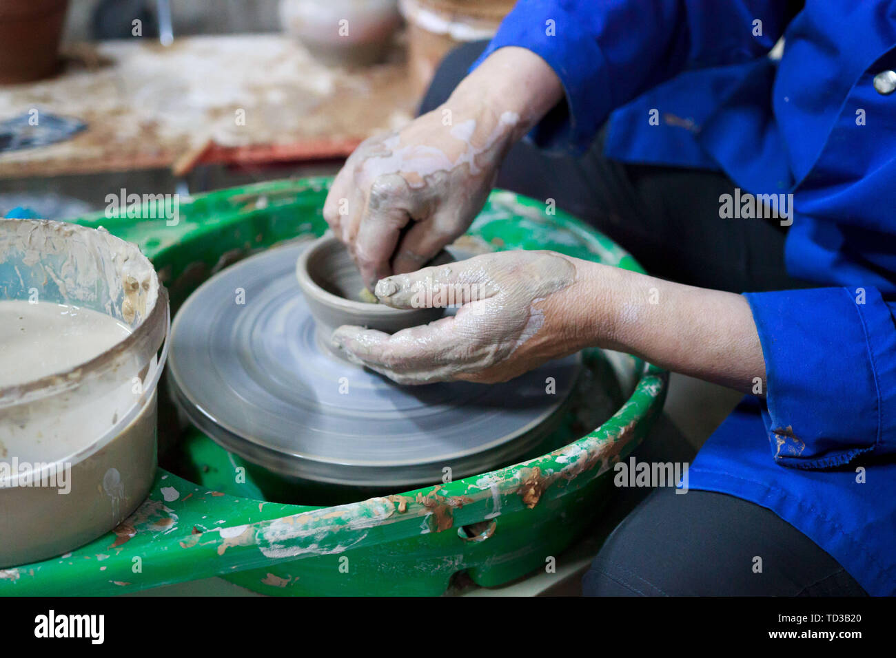 A novice student in the first lesson in pottery tries to make a product from clay on a potter's wheel. reportage Stock Photo