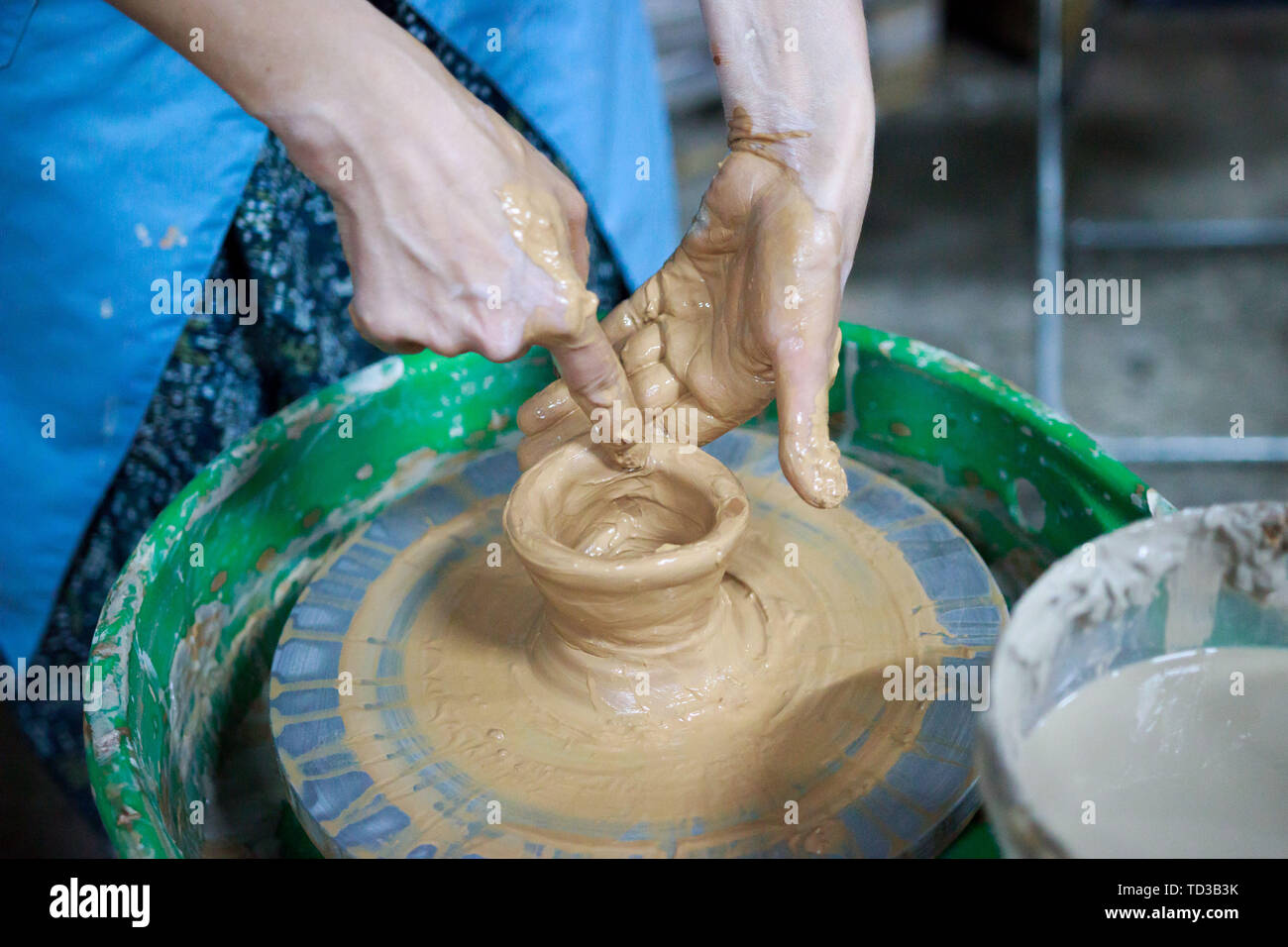 A novice student in the first lesson in pottery tries to make a product from clay on a potter's wheel. reportage. Incorrect hand setting. Stock Photo
