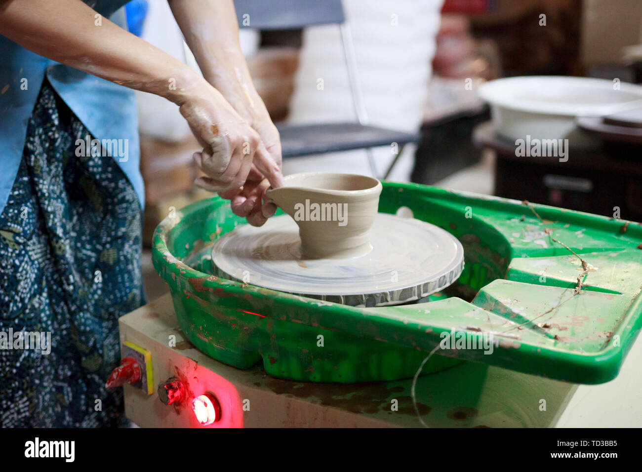 Young woman novice student in the first lesson in pottery tries to make a product from white clay on a potter's wheel. reportage. small sauce pan. mak Stock Photo