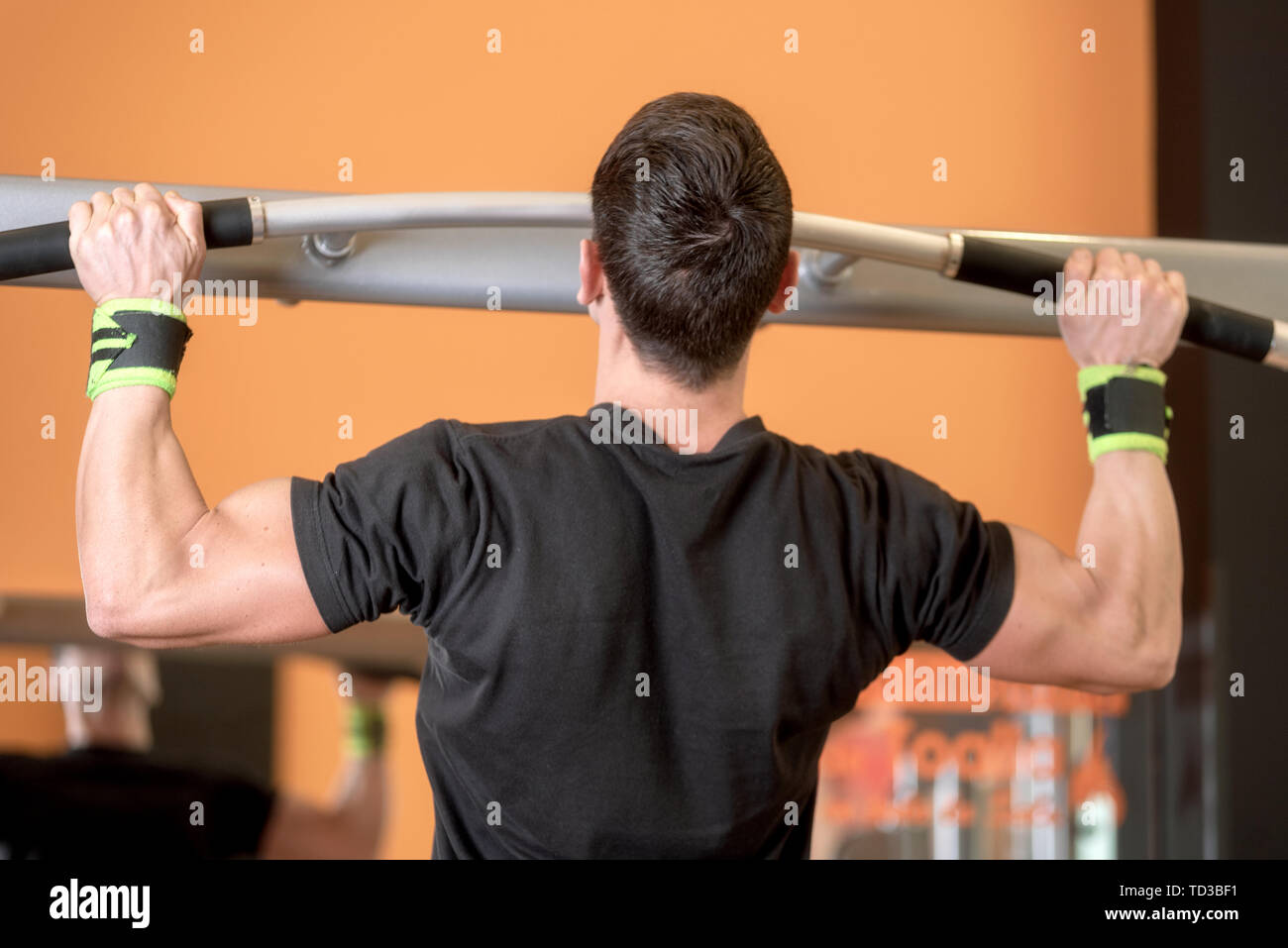 Athlete muscular fitness male model pulling up on horizontal bar in a gym . - Stock Image
