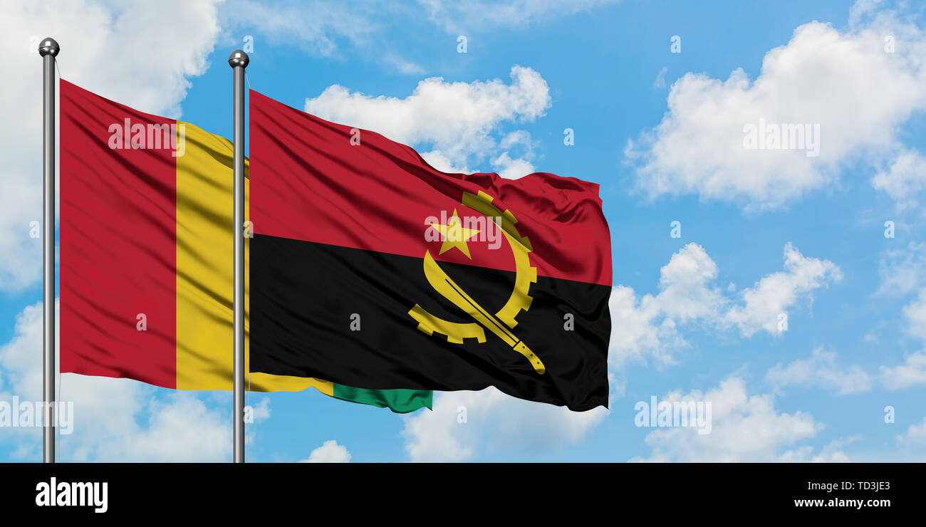 Guinea and Angola flag waving in the wind against white cloudy blue sky together. Diplomacy concept, international relations. - Stock Image