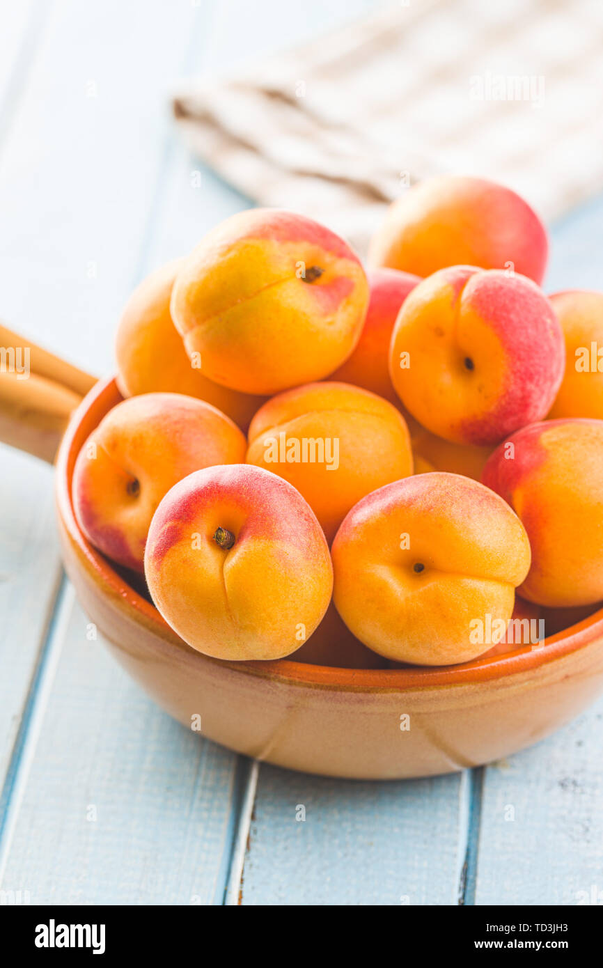 Sweet apricot fruits on blue wooden table. - Stock Image