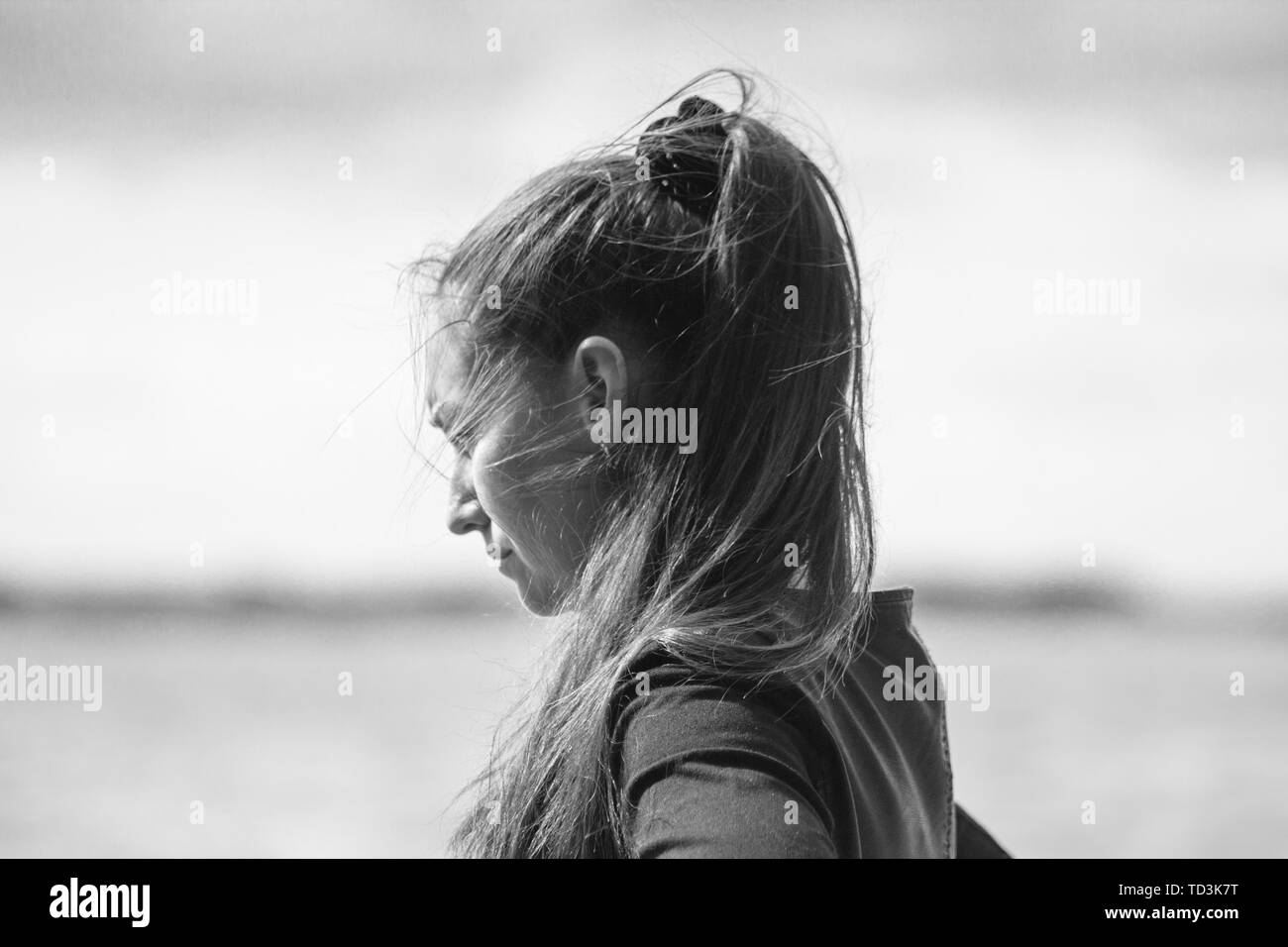 Half-face portrait young woman with long dark ponytail hair fluttering in the wind against the backdrop of the sea. Black and white processing Stock Photo