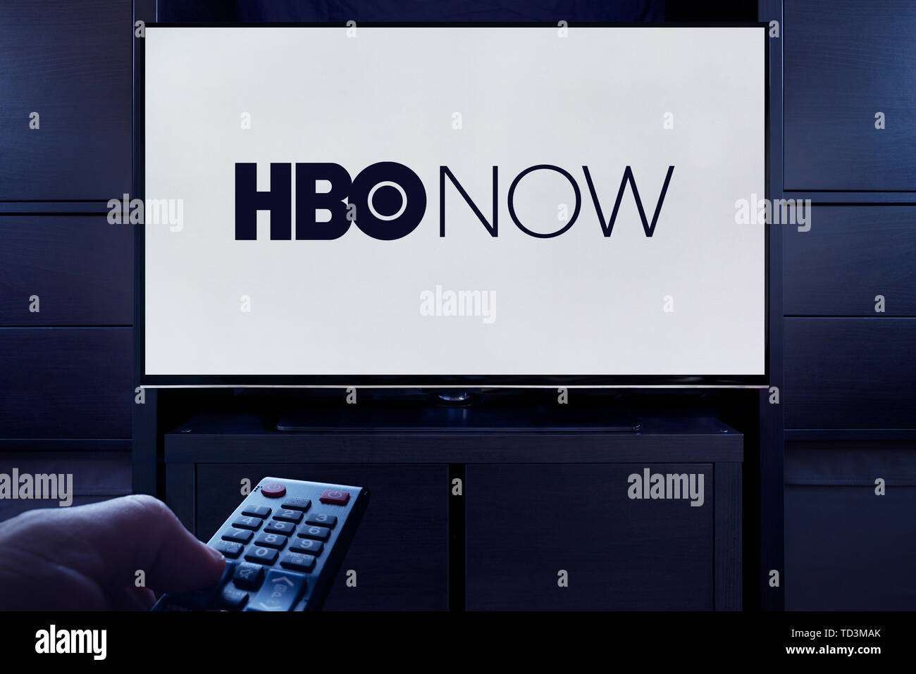 A man points a TV remote at the television which displays the logo for the HBO Now on demand video streaming service (Editorial use only). - Stock Image