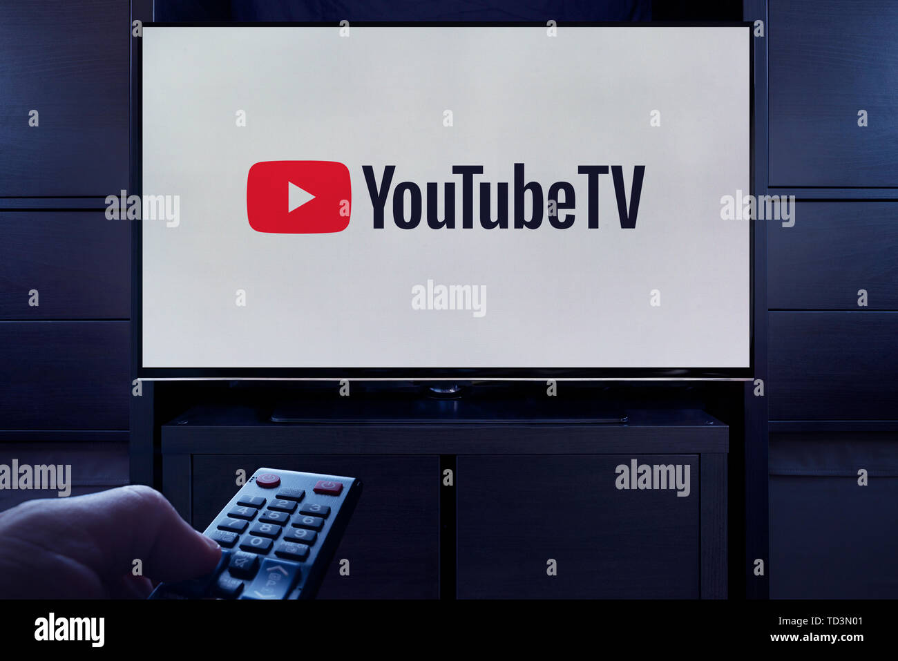 A man points a TV remote at the television which displays the logo for the YouTube TV on demand video streaming service (Editorial use only). - Stock Image