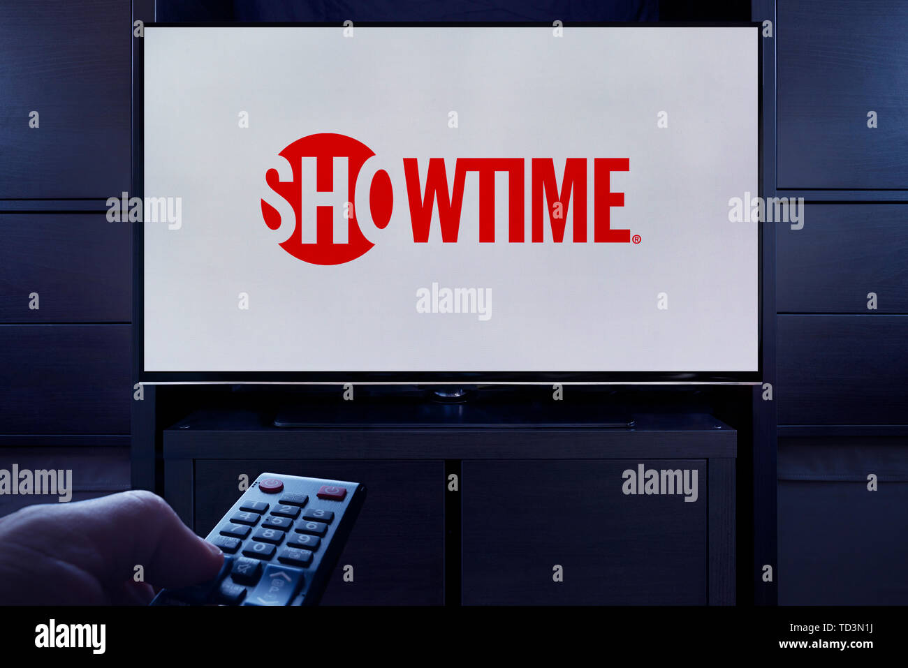 A man points a TV remote at the television which displays the logo for the Showtime on demand video streaming service (Editorial use only). - Stock Image