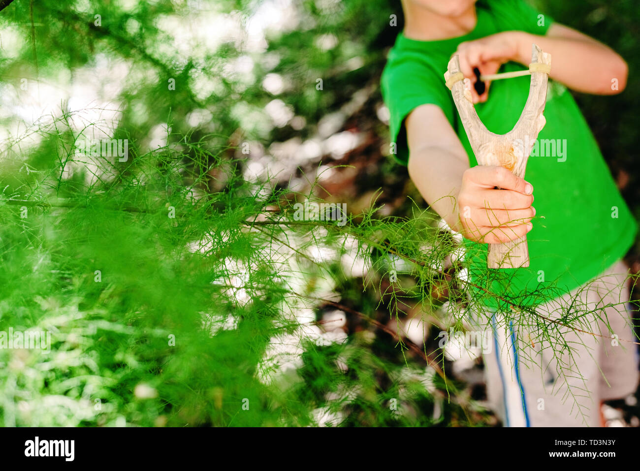 Boy threatening his schoolmates with a slingshot. - Stock Image