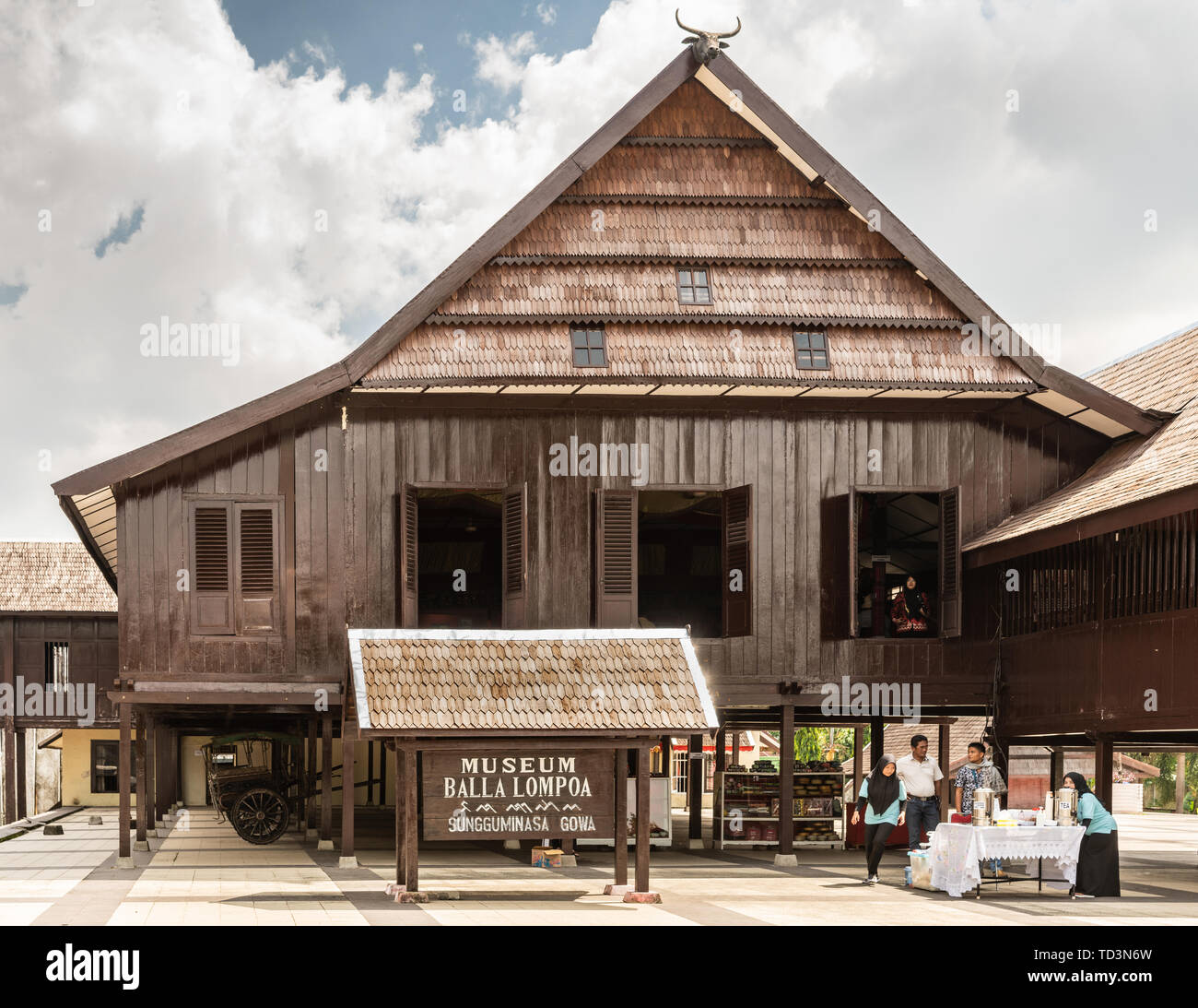 Makassar, Sulawesi, Indonesia - February 28, 2019: Dark brown wooden construction is museum Balla Lompoa, former palace of Gowa Kingdom. People offer  - Stock Image