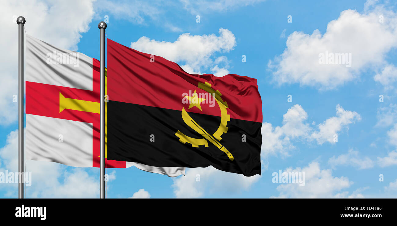 Guernsey and Angola flag waving in the wind against white cloudy blue sky together. Diplomacy concept, international relations. Stock Photo
