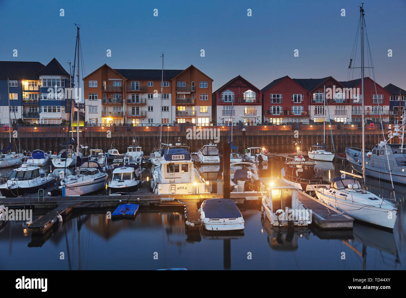 A dusk view of modern harbourside housing, beside the estuary of the River Exe, at Exmouth, Devon, England, United Kingdom, Europe - Stock Image