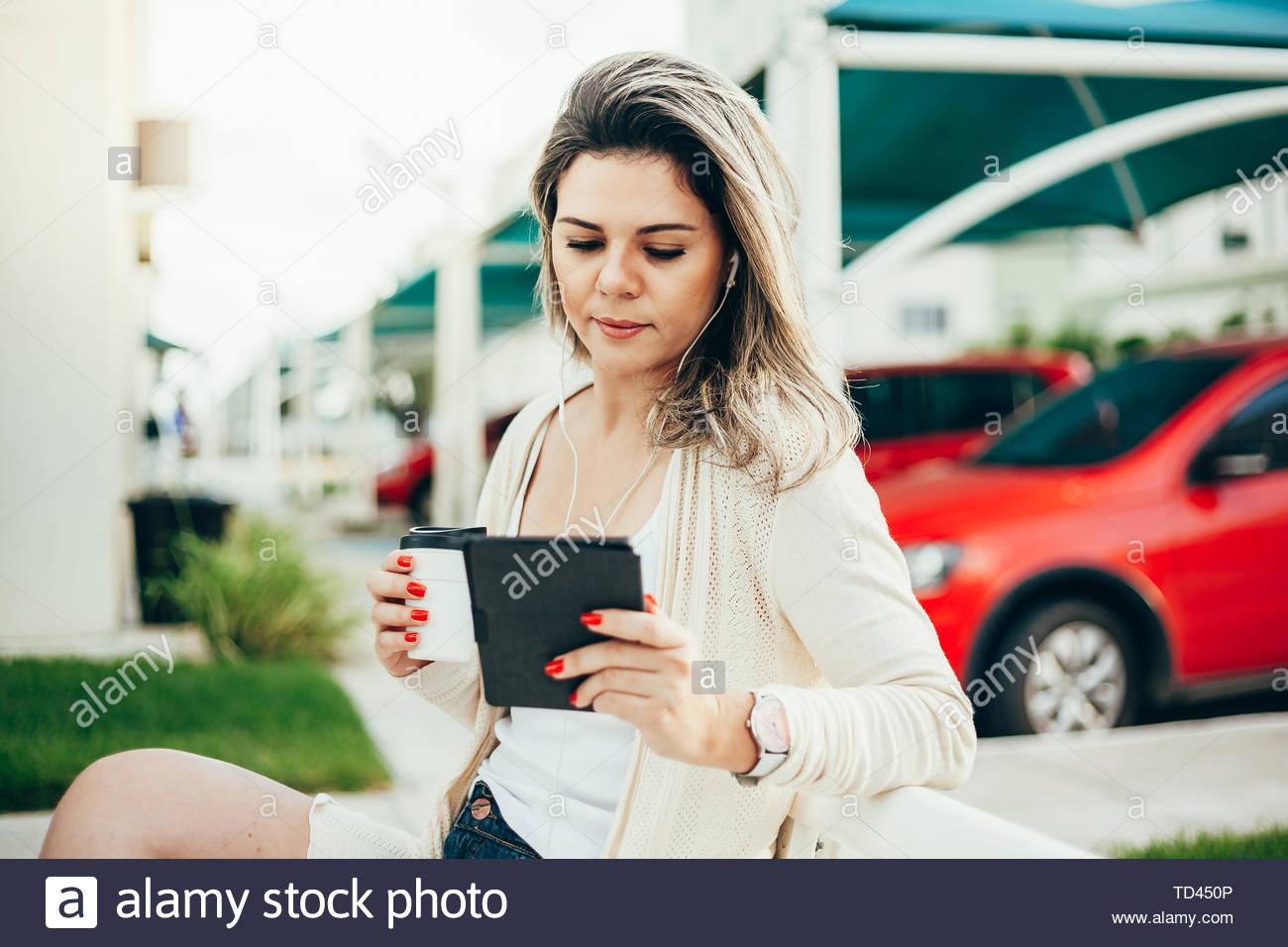 A young woman sits on a bench, holds a coffee cup in her hand and reads an e-book in the city - Stock Image