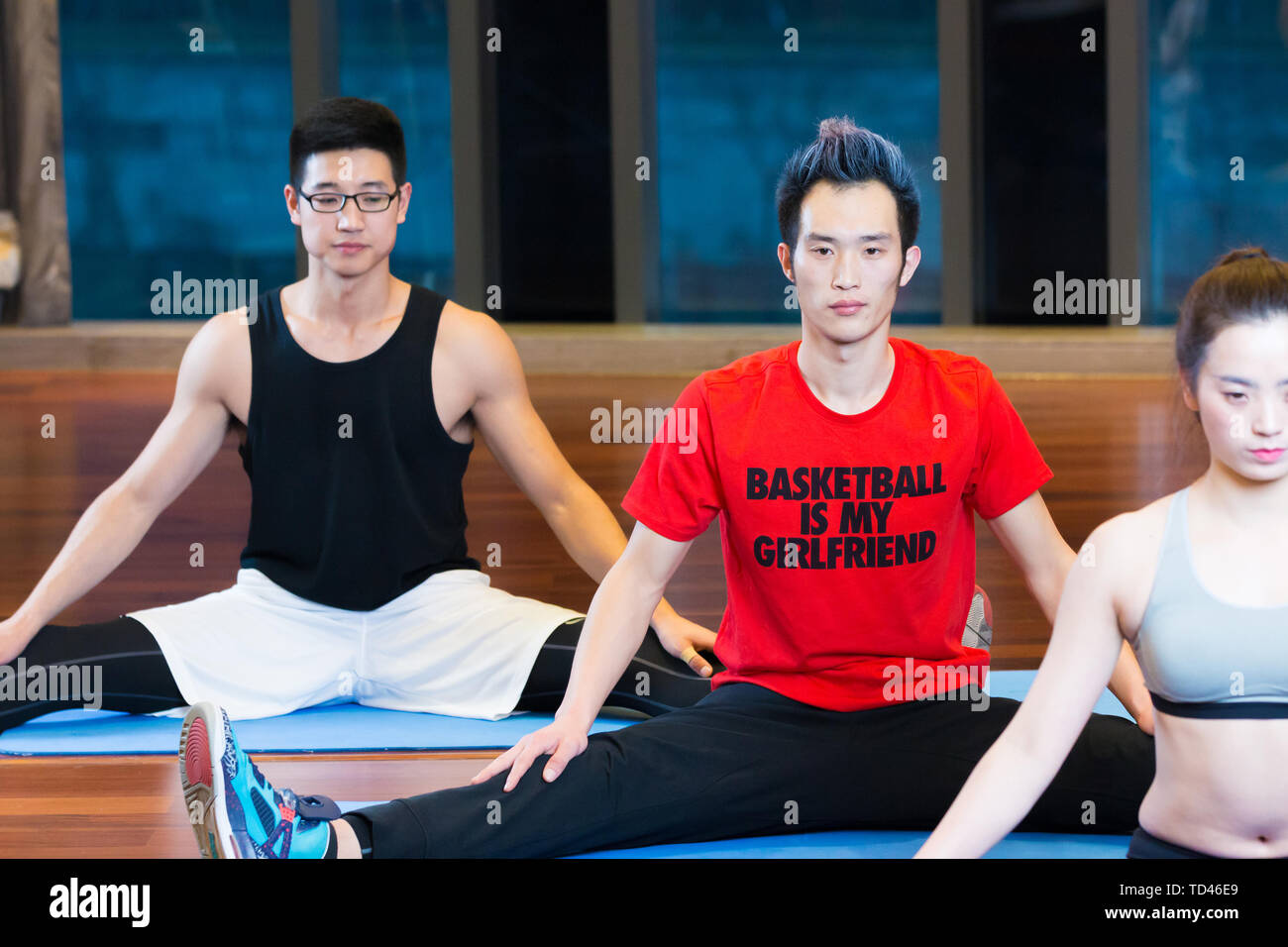 young asian people doing yoga in modern gym - Stock Image