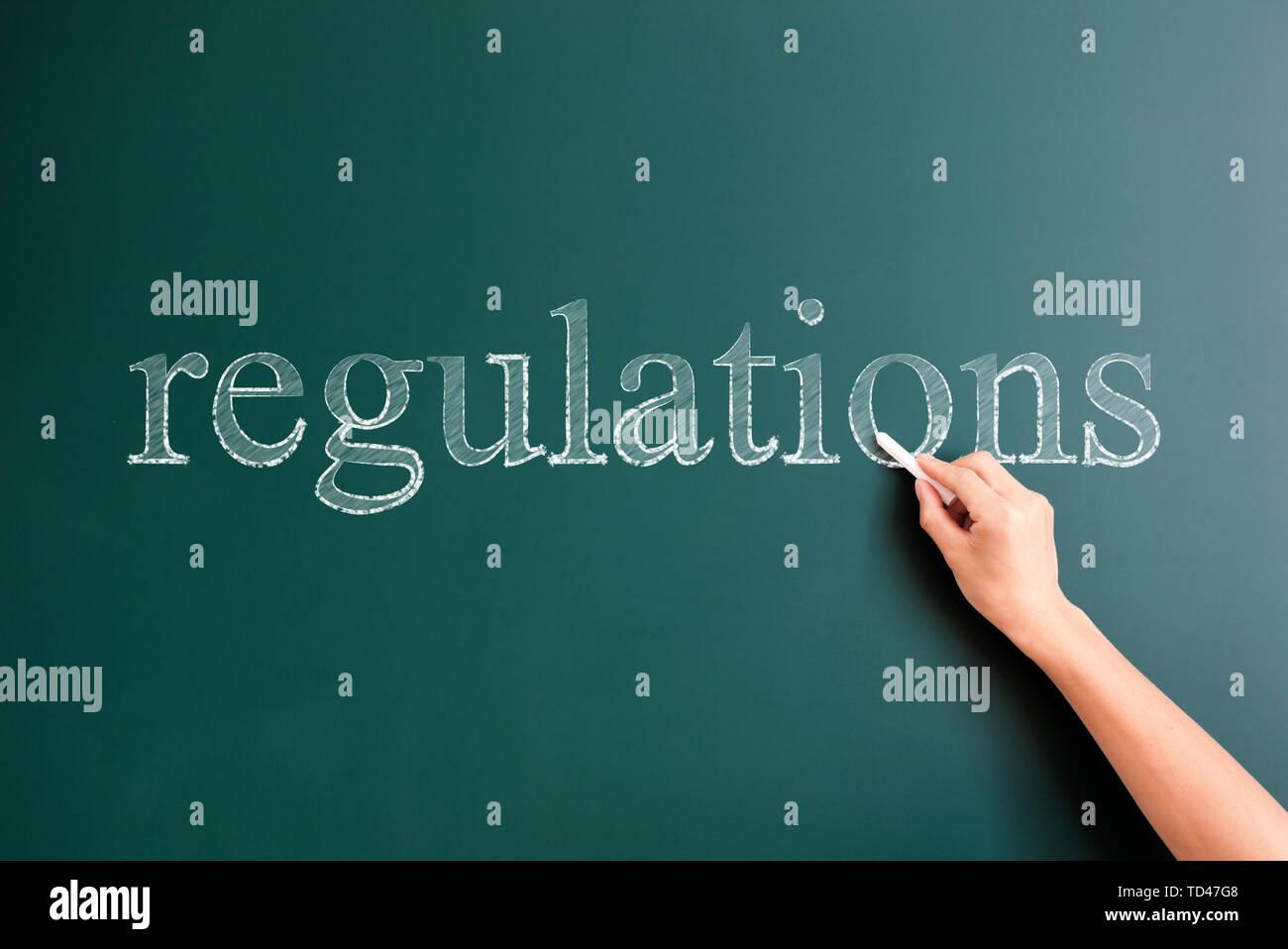 regulations written on blackboard - Stock Image